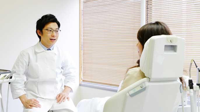 歯列矯正についてのカウンセリングを男性歯科医師から受けている女性